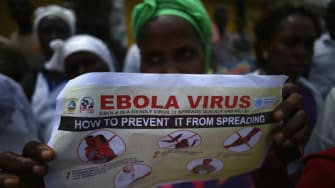 A woman reads a pamphlet on Ebola.