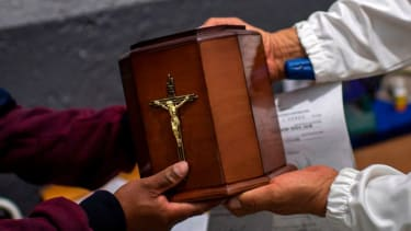 A man receives the urn containing his father's ashes.