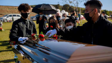 People gather for the funeral of a coronavirus victim.