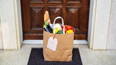 A bag of groceries on a front porch.
