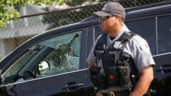 The shattered window of a vehicle hit by a bullet.