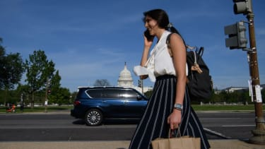 A woman not wearing a face mask speaks on the phone as she walks past the US Capitol in Washington, DC, on April 27, 2021
