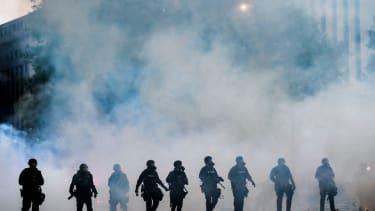 Police officers in Denver after firing tear gas.
