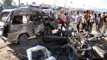 Residents gather at the site of a car bomb attack on April 25 in Baghdad that killed at least eight and wounded 23 others.