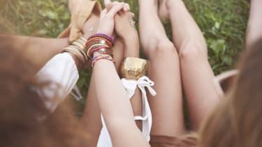 Women holding hands in festival attire.