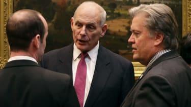 Homeland Security Secretary John Kelly (C) talks with White House Chief Strategist Steve Bannon (R)