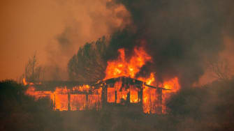 A house burns at the Mendocino Complex fire near Finley, California on July 30, 2018.