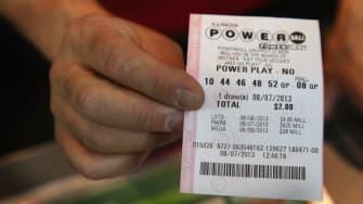 A man hands a customer a Powerball ticket.