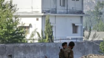 Soldiers stand guard outside Osama bin Laden's Abbottabad compound