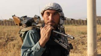 An Afghan police man rests a gun on his shoulder outside Kunduz
