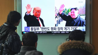 Side by side photos of President Trump and Kim Jong Un on a television