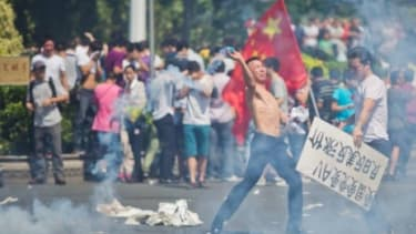 An anti-Japanese protester in Shenzhen, China throws a gas cannister as hundreds of people demonstrate over the disputed Diaoyu Islands.
