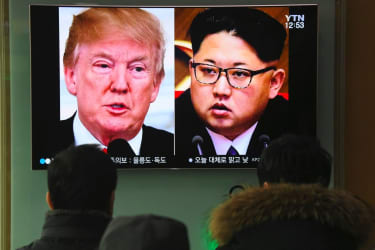 People watch a television news report showing pictures of President Trump and North Korean leader Kim Jong Un at a railway station in Seoul