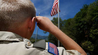 A Boy Scout salutes the American flag.