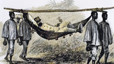 European colonizer carried in a hammock by four African porters.
