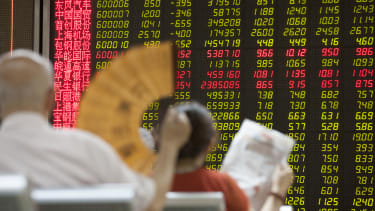 Investors look at a screen projecting Chinese stocks.
