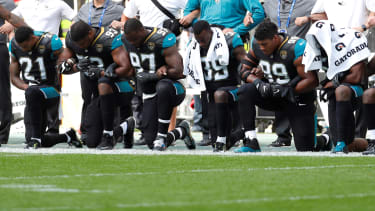 Jacksonville Jaguars players kneel during the U.S. national anthem before a match.