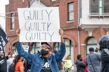 A person holds a sign celebrating Derek Chauvin's guilty verdict.