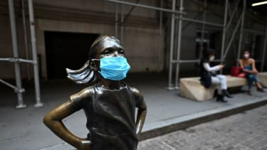 Fearless Girl statue outside the U.S. stock exchange wears a mask.