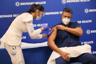 Leonida Lipshy, RN in the COVID unit at the Broward Health Medical Center, gives Jaime Carrillo, M.D. Internal Medicine, Broward Health Imperial Point, a shot of the Moderna COVID-19 vaccine