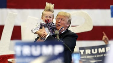 Donald Trump holds a young boy up during a rally.