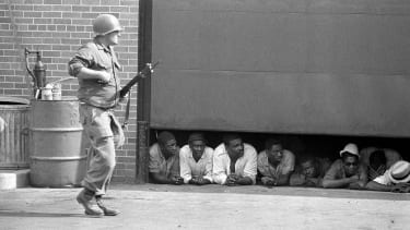 Captured men peer from under a garage door