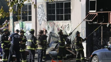 Firefighters work to clear the debris from a doorway following a fire that killed at least nine people at a warehouse in Oakland