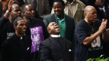 Members of the New Birth Missionary Baptist church worship during Bishop Eddie Long's sermon where he addressed sex scandal allegations.