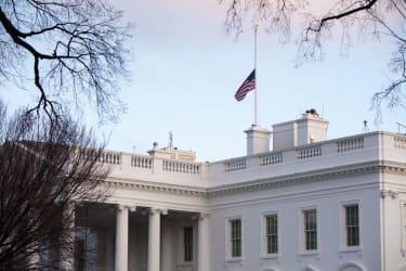 Flag flying half staff over White House.