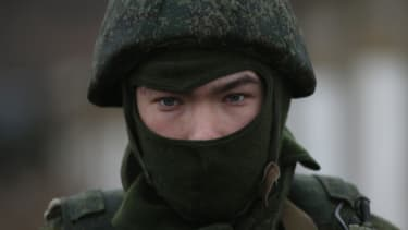 A soldier stands guard near a military base in Crimea