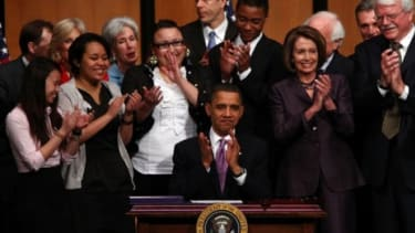 President Obama applauds after signing the health care act in 2010: The Supreme Court will assess, among other things, the controversial individual health care mandate.