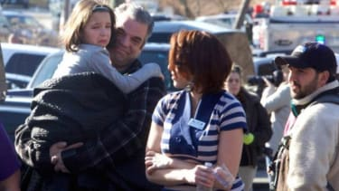 Parents pick up their children outside Sandy Hook Elementary after a deadly school shooting in Newtown, Conn.