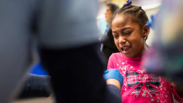 A girl cries as she gets her finger pricked for a lead screening in Flint, Michigan.