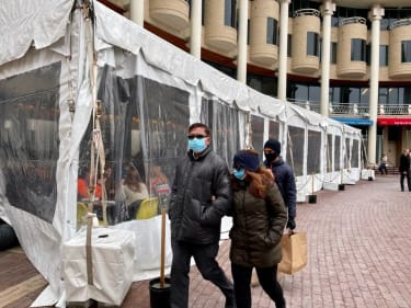 People walk past a plastic covered section outside an eating area at a restaurant in Washington, DC on February 14, 2021.