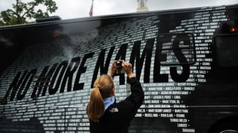 A woman takes a photograph at a Newtown 6 month remembrance event.