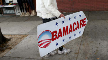 A man holds a sign directing people to sign up for Obamacare.