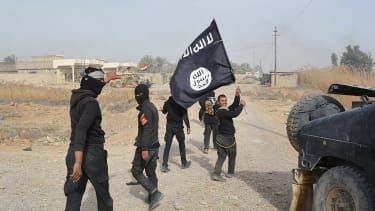 Iraqi government forces carry an ISIS flag they say they captured