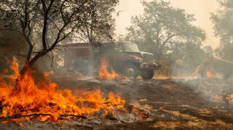 Firefighters douse a hotspot near various homes as the Carr fire continues to burn near Redding, California, on July 28, 2018.