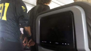 A man is escorted off an American Airlines flight after it landed in Honolulu, Friday, May 19, 2017