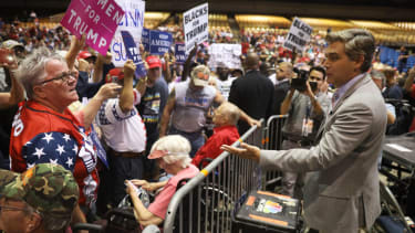 A woman yells at CNN's Jim Acosta before a Trump rally in Tampa.