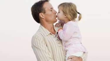 Consider age, some say, when giving your kids a peck on the lips.