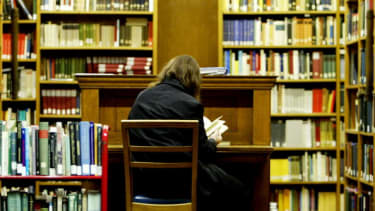 A woman reads in a library.