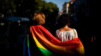 A couple in a rainbow flag.