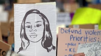 A protester marches with a picture of Breonna Taylor.