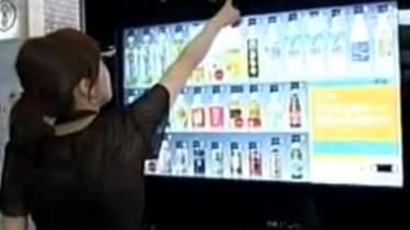 A woman points out the hidden software in a touch-screen vending machine that recognizes gender and age and makes drink suggestions.