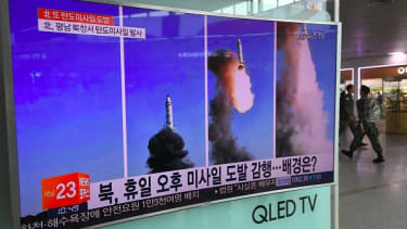 A television screen shows footage of a North Korean missile launch.