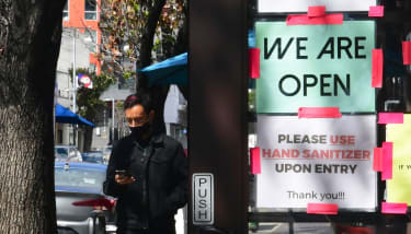 """A """"We Are Open"""" sign is seen on the side of a restaurant as indoor dining reopens in Los Angeles, on March 15, 2021."""