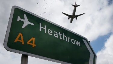 A plane flies over Heathrow Airport.