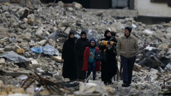 Syrian walk the rubble of their former neighborhood in eastern Alyppo.
