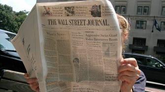 A woman reads The Wall Street Journal.